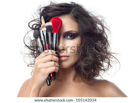 closeup portrait of attractive  caucasian young woman brunette isolated on white studio shot looking at camera makeup face skin hand brushes - stock photo