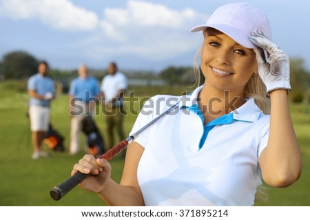 Closeup portrait of attractive female golfer on the fields, smiling, looking at camera.