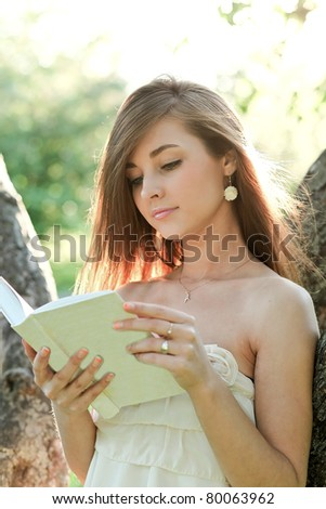 closeup portrait of attractive girl with book in the park - stock photo