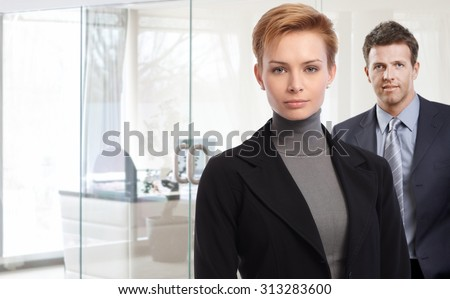 Closeup portrait of attractive young businesswoman and male colleague at bright office. - stock photo