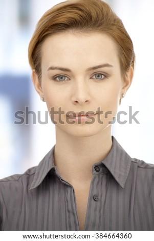 Closeup portrait of attractive young businesswoman with short blonde hair looking at camera. - stock photo
