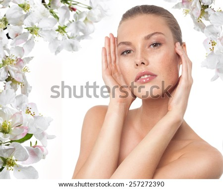 closeup portrait of attractive young  caucasian woman  isolated on white studio shot lips  face hair head and shoulders looking at camera spring flowers - stock photo