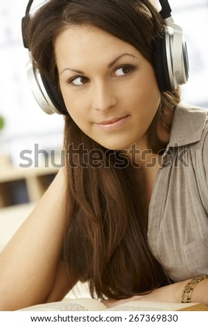 Closeup portrait of attractive young woman with headphones and book, smiling, looking away. - stock photo