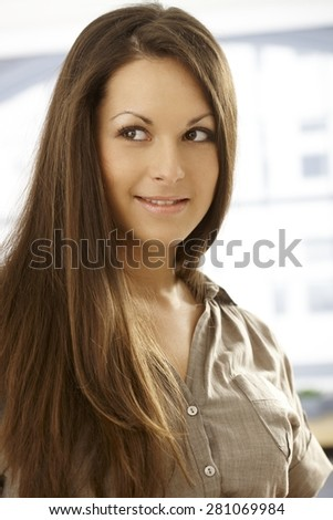 Closeup portrait of attractive young woman with long hair, looking away. - stock photo