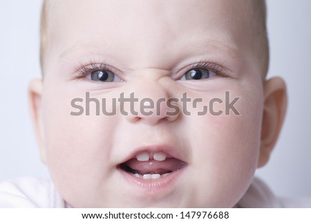 Closeup portrait of baby boy making funny face - stock photo