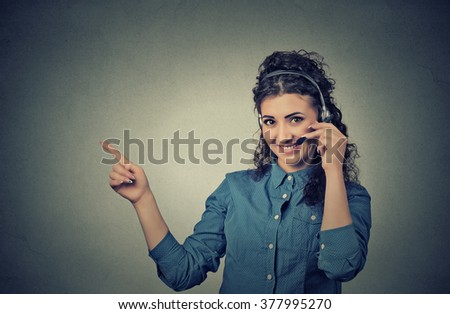 Closeup portrait of beautiful, adorable smiling female customer representative with phone headset pointing at copy space isolated on gray wall background. Positive human emotions, facial expressions  - stock photo