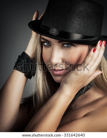 Closeup portrait of beautiful blond female with perfect makeup wearing stylish hat and bracelet posing over gray background, fashionable accessories for party