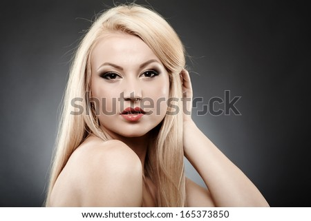 Closeup portrait of beautiful blonde looking sexy over shoulder and holding hair - stock photo