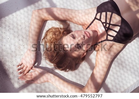 Closeup portrait of beautiful blonde woman wearing black swimwear sitting on a rooftop in a sunny summer day with shadow net reflection from metal sunshade on her face over black wall