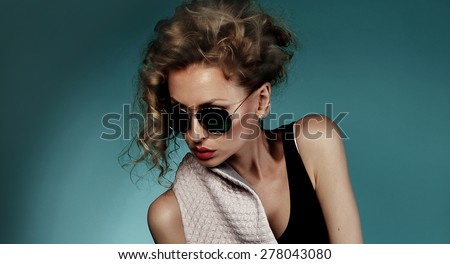 Closeup portrait of beautiful blonde woman wearing fashionable sunglasses. Blue background.