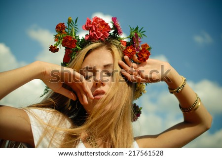 closeup portrait of beautiful blonde young lady wearing flower crown having fun enjoying herself relaxing eyes closed on summer blue sky copy space background - stock photo