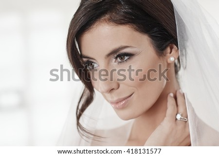 Closeup portrait of beautiful bride in veil, looking away.