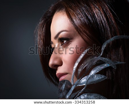 Closeup portrait of beautiful brunet woman with silver leaves decoration over dark gray background, fashion look, celebrating Christmas holidays
