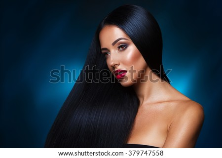 closeup portrait of beautiful brunette girl with healthy straight dark hair and holiday makeup against abstract 