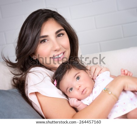 Closeup portrait of beautiful brunette mother with cute newborn daughter relaxing on sofa at home, happy young arabic family - stock photo