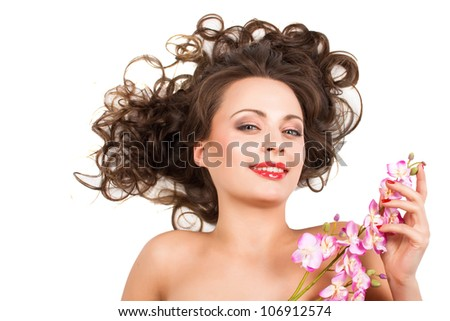 Closeup portrait of beautiful brunette with delicate flowers - stock photo