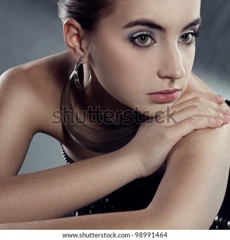 closeup portrait  of beautiful brunette woman wearing silver jewellry - stock photo