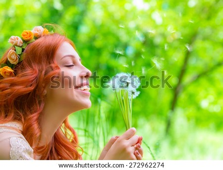 Closeup portrait of beautiful cheerful female holding in hands dandelion flowers and closed eyes of pleasure, enjoying beauty of spring nature - stock photo