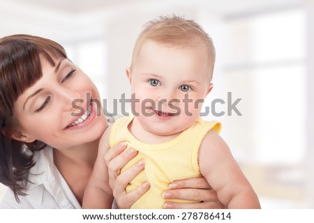 Closeup portrait of beautiful cheerful mother having fun with adorable little daughter at home, happy motherhood concept - stock photo