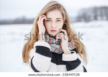 closeup portrait of beautiful cute serious young girl with long hair with black and white striped jacket  on natural background in field. Winter outdoor photo - stock photo