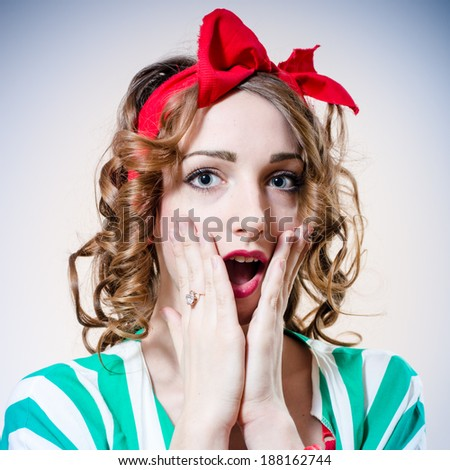 closeup portrait of beautiful elegant blonde woman with big blue eyes and red lips open mouth in surprise looking at camera on light blue background - stock photo