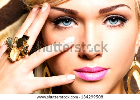 Closeup portrait of beautiful face of sexy woman with fashion makeup and gold ring on finger - stock photo