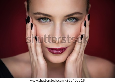 Closeup portrait of beautiful fashion model over dark red background, pretty woman with stylish makeup, beauty salon photo - stock photo