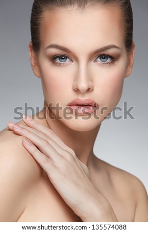 closeup portrait of beautiful female face with her hand on shoulder over gray background - stock photo
