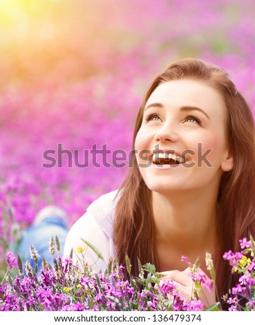 Closeup portrait of beautiful female laying down in fresh pink floral field, warm sunset light, spring nature, vacation and leisure concept - stock photo