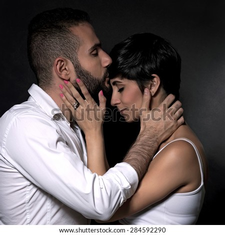Closeup portrait of beautiful gentle couple in love, kissing with closed eyes of pleasure over black background, romantic relationship
