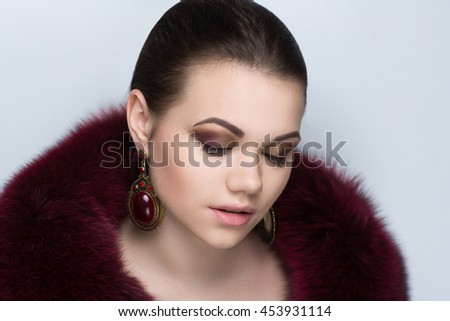 Closeup portrait of beautiful girl woman lady with make up studio styling. Luxury makeup Bright black eyes, shiny beige lips lipstick. Professional photo exclusive model vip person, gray background