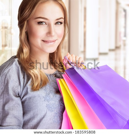 Closeup portrait of beautiful happy woman doing purchase in shopping center, carrying colorful paper bags, spending money concept - stock photo