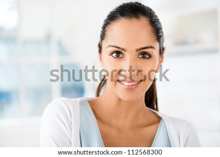 Closeup portrait of beautiful Indian woman smiling at camera - stock photo