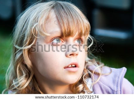 Closeup portrait of beautiful little blond girl looking up with amazement