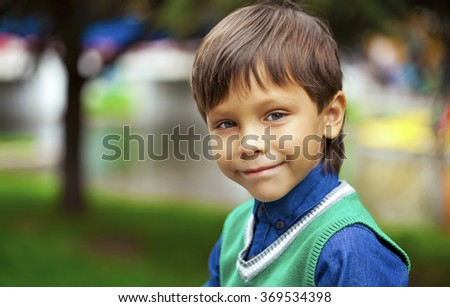 Closeup portrait of beautiful little boy on background summer park  - stock photo