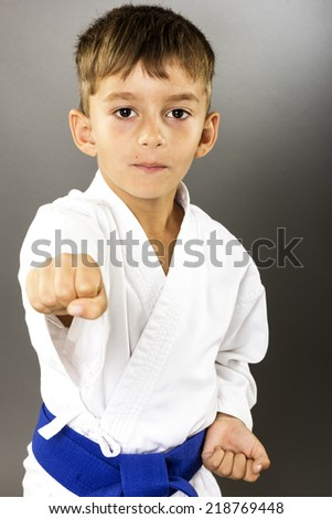 Closeup portrait of beautiful little boy training karate isolated on gray background