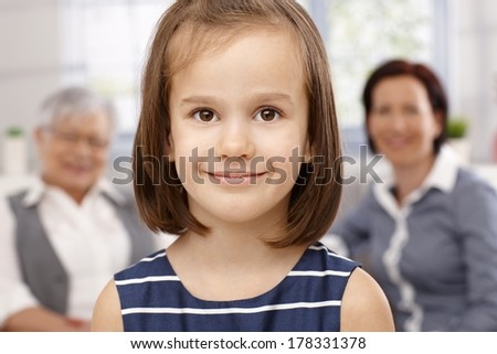 Closeup portrait of beautiful little girl smiling, mother and granny watching from behind. - stock photo