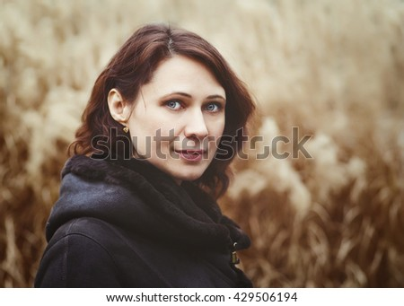 Closeup portrait of beautiful middle age white caucasian brunette woman with green eyes in coat jacket on fall autumn day outside looking in camera on yellow rye background - stock photo