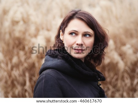 Closeup portrait of beautiful middle age white caucasian brunette woman with green eyes in coat jacket on fall autumn day outside looking away on yellow rye background - stock photo