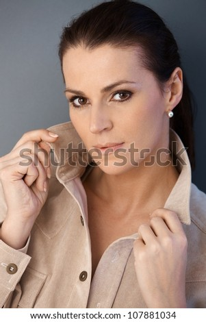 Closeup portrait of beautiful middle aged woman posing in studio, grey background. - stock photo