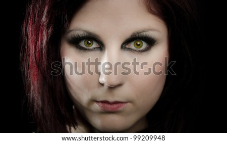 Closeup portrait of beautiful model with intense green eyes and a dark background - stock photo