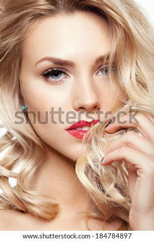 Closeup portrait of beautiful model with perfect skin and bright makeup. Hand next to her face. Looking at camera