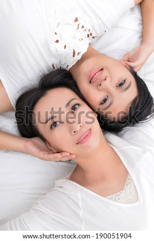 Closeup portrait of beautiful mother and daughter laying down on the white background - stock photo
