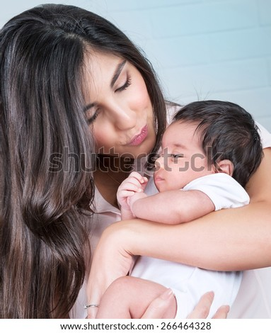 Closeup portrait of beautiful mother kissing cute little baby, having fun at home, enjoying parenthood, love and happiness concept - stock photo