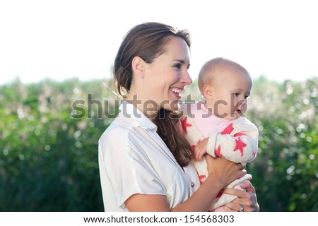 Closeup portrait of beautiful mother smiling and holding cute baby