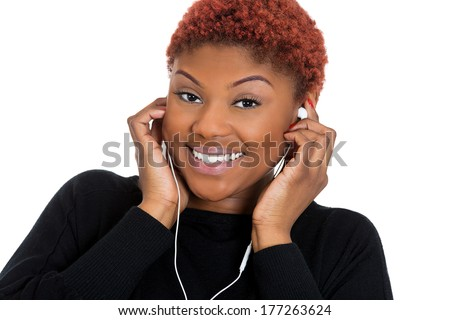 Closeup portrait of beautiful pretty happy young woman with ear buds listening to music on electronic handheld sound player, isolated on white background. Positive emotion facial expression feelings. - stock photo