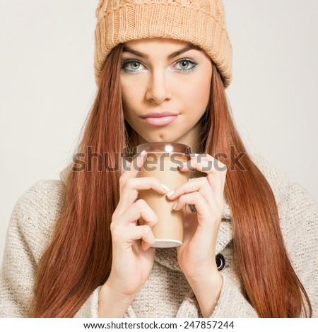 Closeup portrait of beautiful redhead teenage girl with beige knit beanie hat and takeaway coffee. Square format, retouched, instant filter look. - stock photo