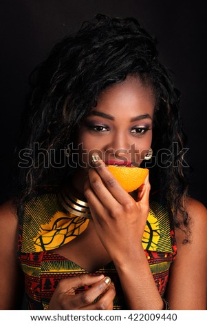 Closeup portrait of beautiful sexy black young woman model with bright makeup with perfect clean skin and orange in hand. Funny fashion mulatto model with orange slice. African-american fashion style.