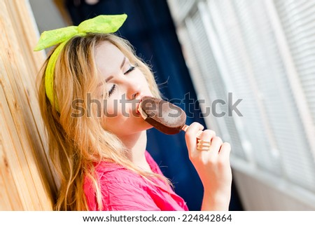 closeup portrait of beautiful sexy young blonde woman with eyes closed in pleasure enjoying eating indoors ice cream on the window blinds copy space background - stock photo