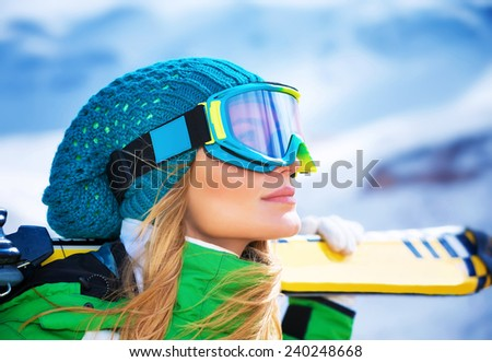 Closeup portrait of beautiful skier girl wearing mask and holding ski, enjoying winter holidays - stock photo